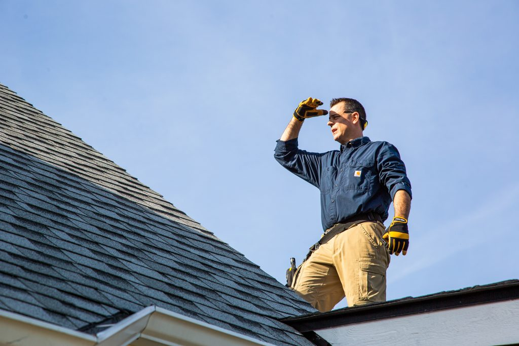 Trevor standing on a roof performing an inspection